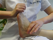 A Bowen move being applied to a patient's ankle